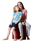 Two girls sitting on a stool