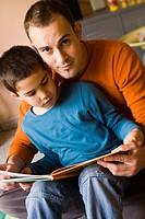 Portrait of a father reading to his son
