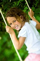 Portrait of a girl swinging on a swing