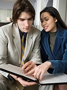 Close_up of a young man and a young woman sitting looking at a file