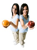 High angle view of two teenage girls holding an apple and an orange
