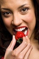 Portrait of a young woman eating a strawberry