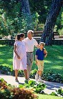 Couple with pregnant woman and boy strolling in park