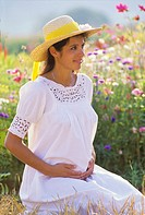 Pregnant woman portrait in flower garden