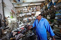 An indian mechanic repair a fridge component in a repair workshop  Ras Al-Khaimah  United Arab Emirates
