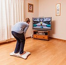 A 9 year old boy playing on a Nintendo Wii Fit board