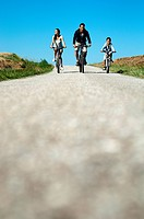 A family on bikes, cycling on a country road