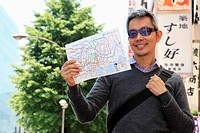 Man holding a map on the streets of Japan