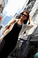 Young woman wearing sunglasses walking on the street, Japan
