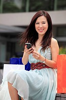 Woman sitting with shopping bags holding phone and smiling.