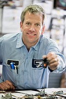Portrait of a mechanic leaning against a workbench