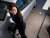 High angle view of a young woman refueling her car