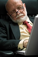 Close_up of a businessman sleeping in front of a laptop