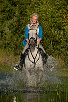 Young woman riding a Hanoverian horse through a lake