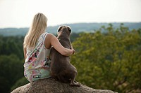 Woman sitting with a Labrador Retriever on a stone