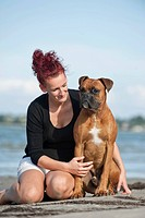 Woman sitting with a Boxer at the beach, Baltic Sea, Mecklenburg-Western Pomerania, Germany, Europe