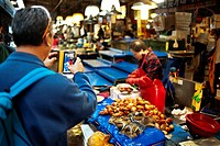 A man uses a smart phone to take a photograph at the Noryangjin Fish Market, Seoul, South Korea, Asia