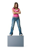 Portrait of a teenage girl standing on a blank sign with her arms crossed