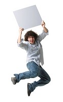 Portrait of a teenage boy holding a blank sign and jumping in mid_air