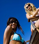 Low angle view of two young women on the beach