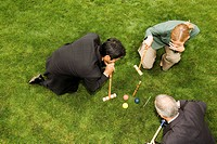 High angle view of two businessmen and a businesswoman playing croquet