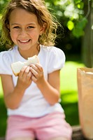 Portrait of a girl eating slice of bread