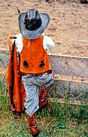 A young cowboy looks through the fence at a rodeo