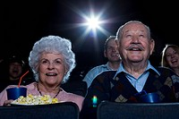 Man and woman watching film at movie theater smiling
