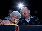 Man and woman watching movie in theater crying with popcorn