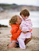 Two girls on beach embracing and smiling