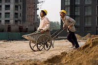 Construction worker giving other worker ride in wheelbarrow
