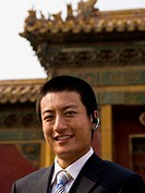 Businessman with headset smiling outdoors