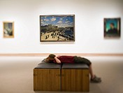 Boy laying down on bench in art gallery with hat covering face