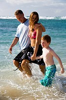 Couple with young boy walking in water on beach
