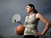 Woman holding basketball with net in background