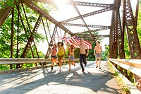 Group of friends running on bridge holding american flag