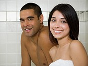 Man and woman in steam bath with towels smiling
