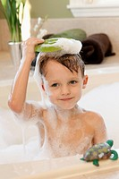Boy holding bar of soap above head in bath