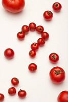 Small tomatoes arranged into a question mark, surrounded by different sized tomatoes