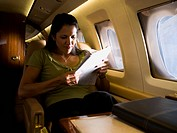 Businesswoman sitting in an airplane and reading a newspaper
