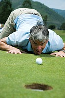 Man kneeling near a golf hole