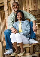 Portrait of a young couple sitting on a staircase and smiling