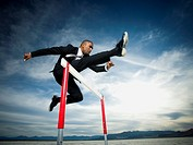 Low angle view of a businessman jumping over a hurdle in a race