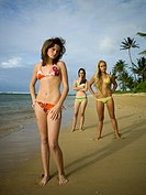 Portrait of three teenage girls standing on the beach