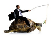 Businessman riding sea turtle with carrot on stick