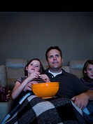 Father and daughters watching movie in home theater