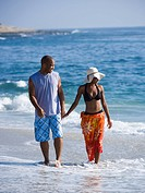 WR0915836 Couple walking hand in hand on beach
