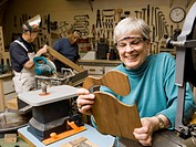 Mature woman in wood shop smiling