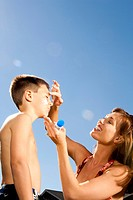 WR0921304 Woman applying sunscreen lotion to boys face