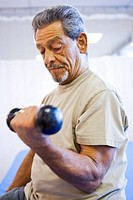 Man with one leg sitting and exercising with weights